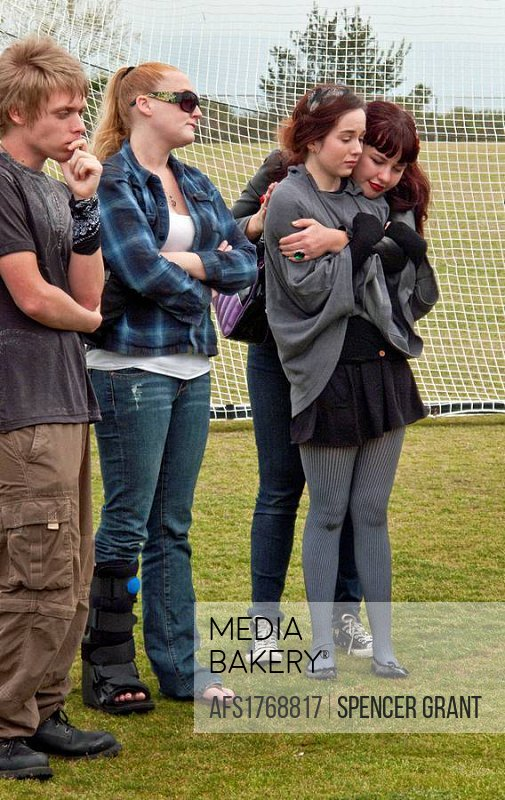 Friends of a young adult suicide comfort each other as they mourn at an outdoor memorial service in a public park in Laguna Beach, CA