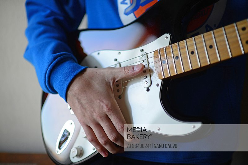Interior portrait of teenager playing the electric guitar.