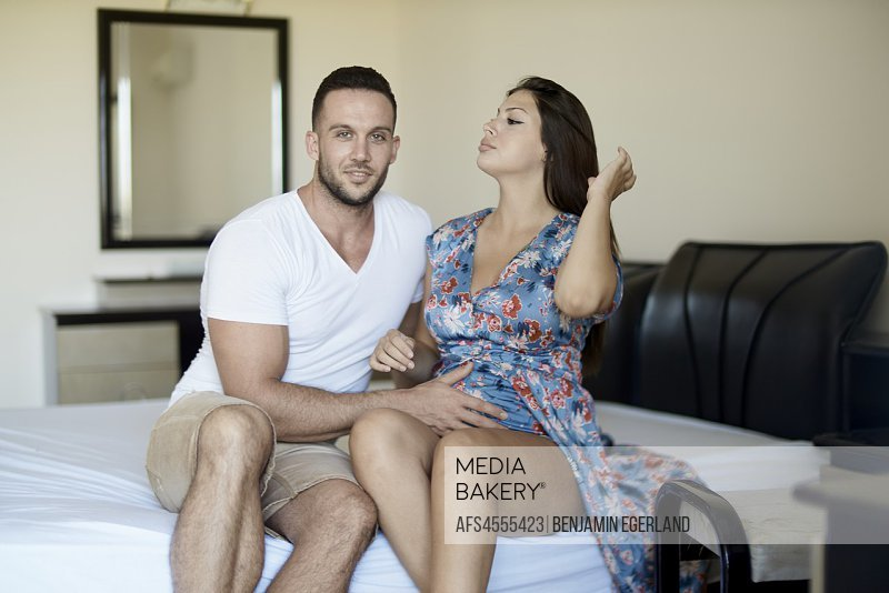 young couple sitting on bed, pregnancy, relationship.