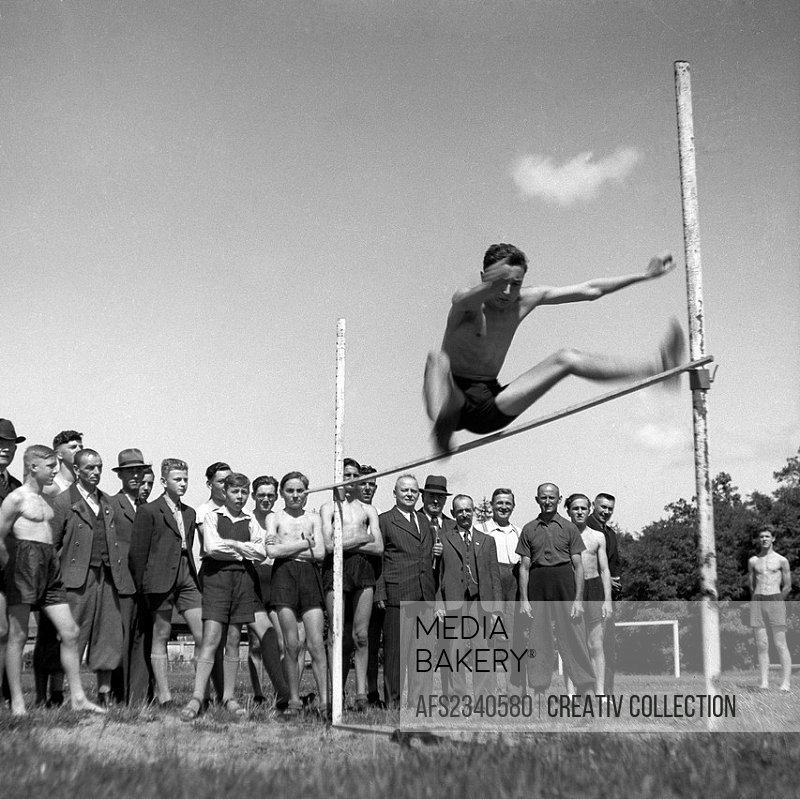 people watching an athlete doing high jump in a contest