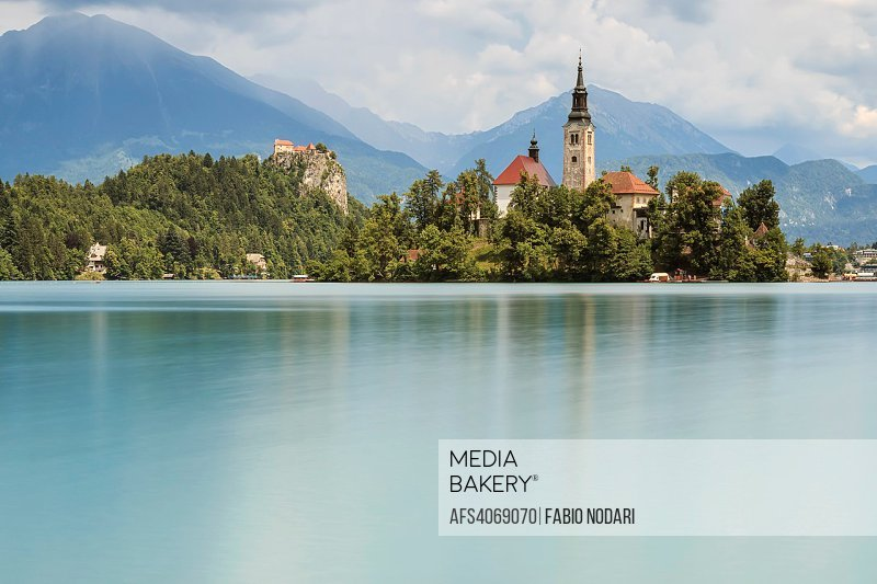 Beautiful view of Lake Bled with Island, Church And Castle With Mountain Range (Stol, Vrtaca, Begunjscica) In The Background- Bled, Slovenia, Europe.