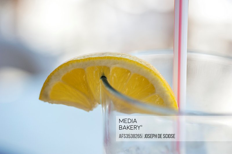 A lemon wedge on the edge of a water glass.