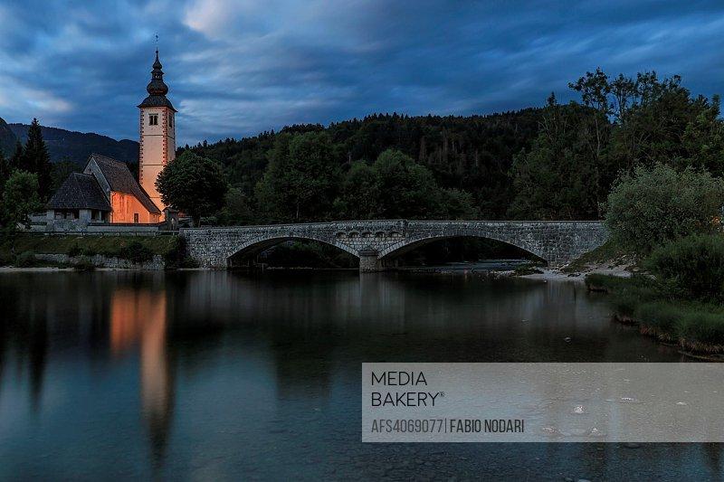 Bohinj, Slovenia - June 5, 2017: Church of St John the Baptist in Lake Bohinj, a famous destination not far from lake Bled in Slovenia, at sunset.