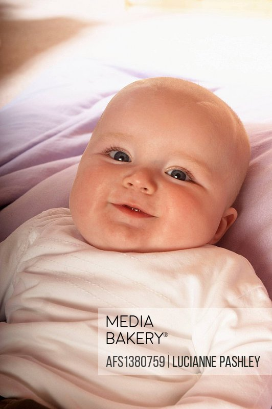 5 month old baby lying on his back smiling into camera