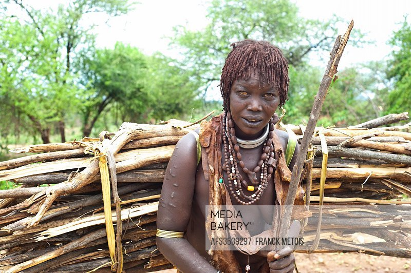 Woman belonging to the Hamer tribe ( Omo valley, Ethiopia). She is carrying firewood.