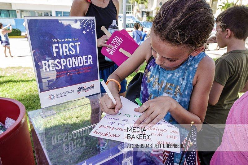 Florida, Miami Beach, Ocean Drive, Veterans Day Parade activities, write letter gratitude American heroes first responders, girl, writing,