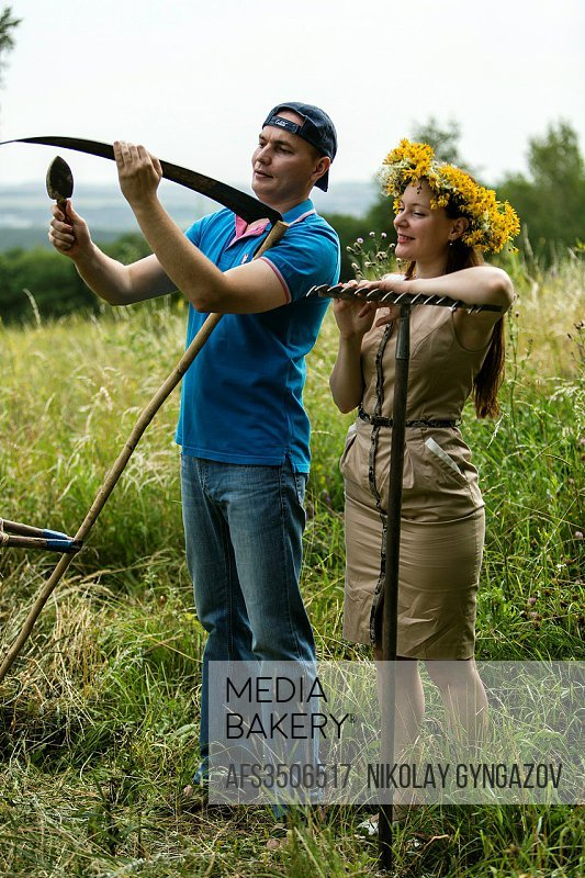 Young couple with an agricultural tool in the field.