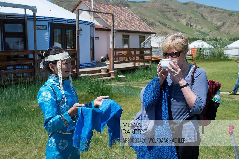 Woman in traditional costume welcoming tourist with milk (traditionally fermented mares milk) at Munkh Tenger ger camp in Kharakhorum, Mongolia.