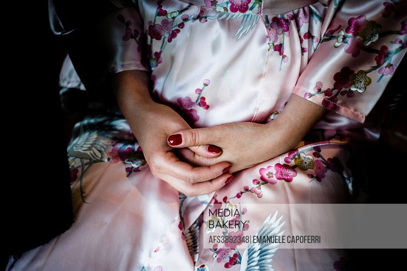 Hands clasped woman resting in her lap