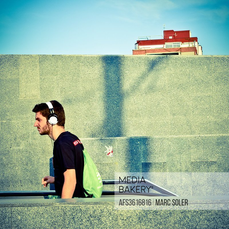 Young man walking and listening through headphones outdoors in summer, wall background. Barcelona, Catalonia, Spain.