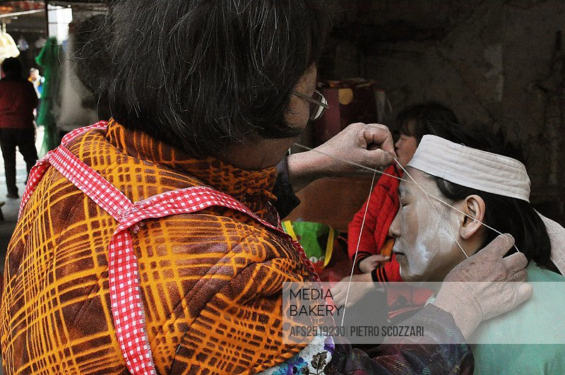 Dongguan (China): a street beautician plucking a client's eyebrows with a thread in the city's center old market