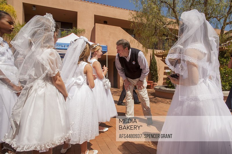 The deacon of a Laguna Niguel, CA, Catholic church greets formally dressed girls on the Sunday morning of their First Communion.