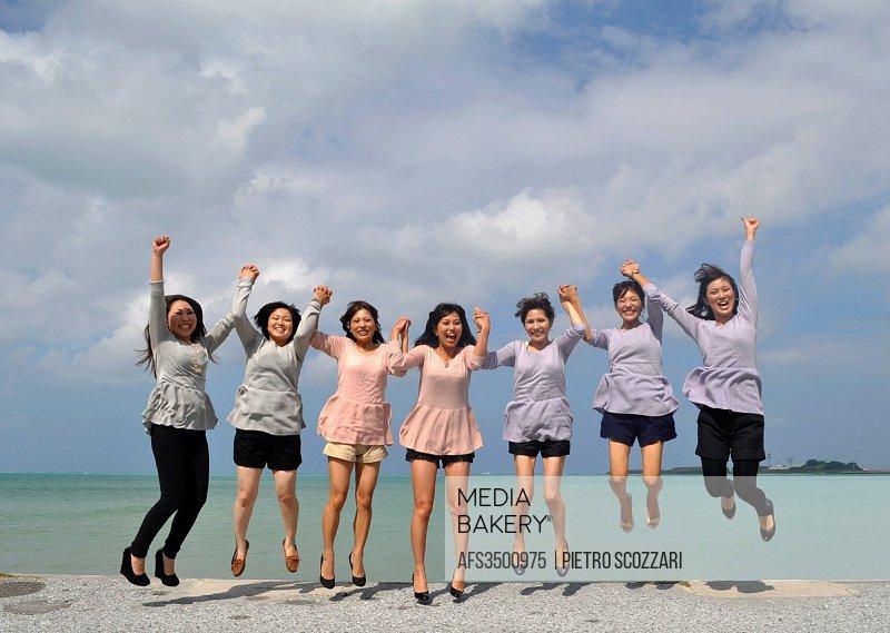 Naha, Okinawa, Japan: Japanese women jumping for happiness during their 30th birthday at Senaga-jima