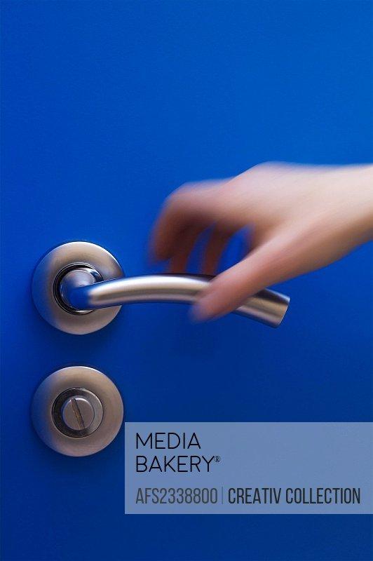 hand opening a blue door