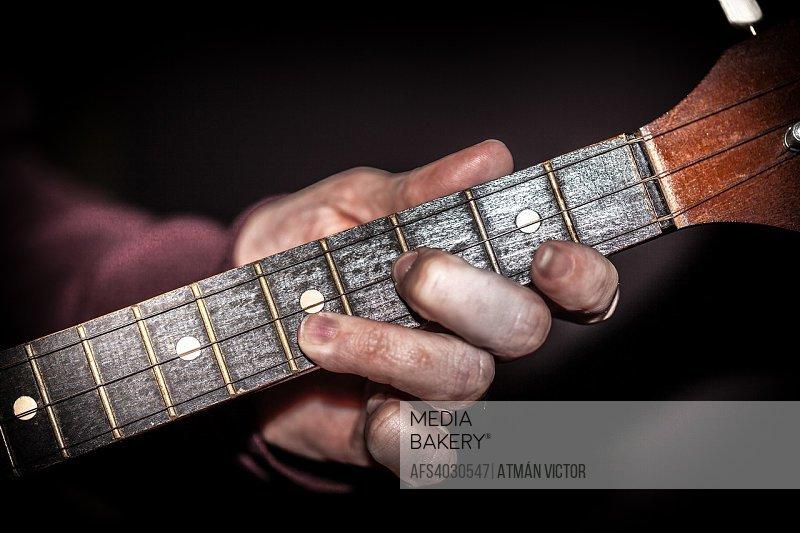 woman playing the guitar neck of a balalaika