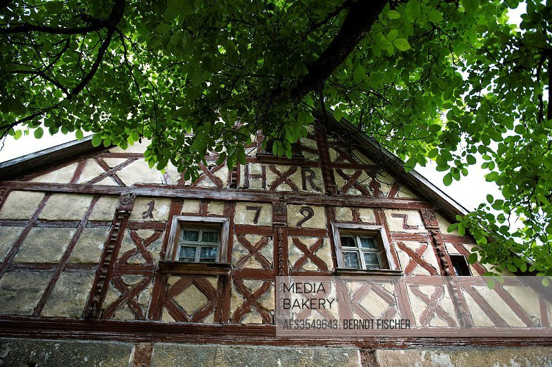 Old framework house from 1792, baroque style, walnut tree, Franconian village, Bavaria, Germany.