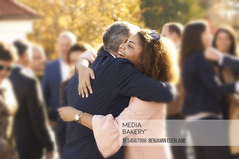 two people embracing at family gathering, celebration, reunion, hugging, in Pöcking, Starnberg, Bavaria, Germany.