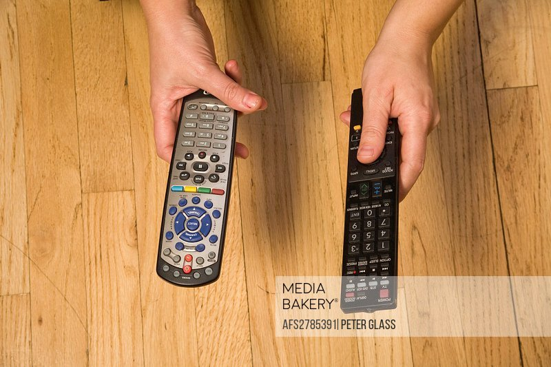 Woman´s hands holding remote controls