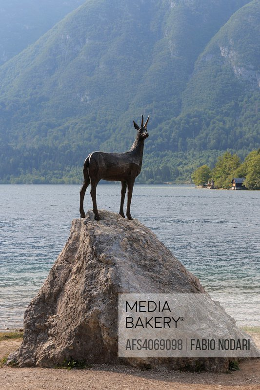 Gold Horned Chamois statue with Bohinj lake in background, Slovenia.