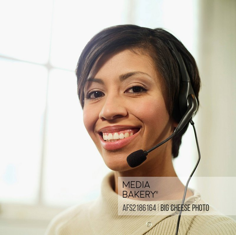 Portrait of a smiling, multi_ethnic woman, 30s, wearing a telephone headset.