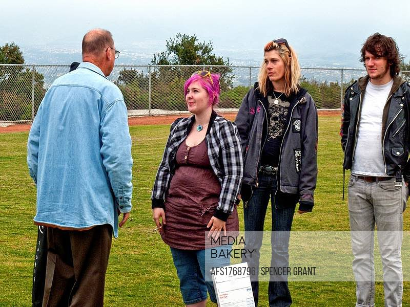The father of a young adult suicide talks with friends of his late daughter at an outdoor memorial service at a public park in Laguna Beach, CA