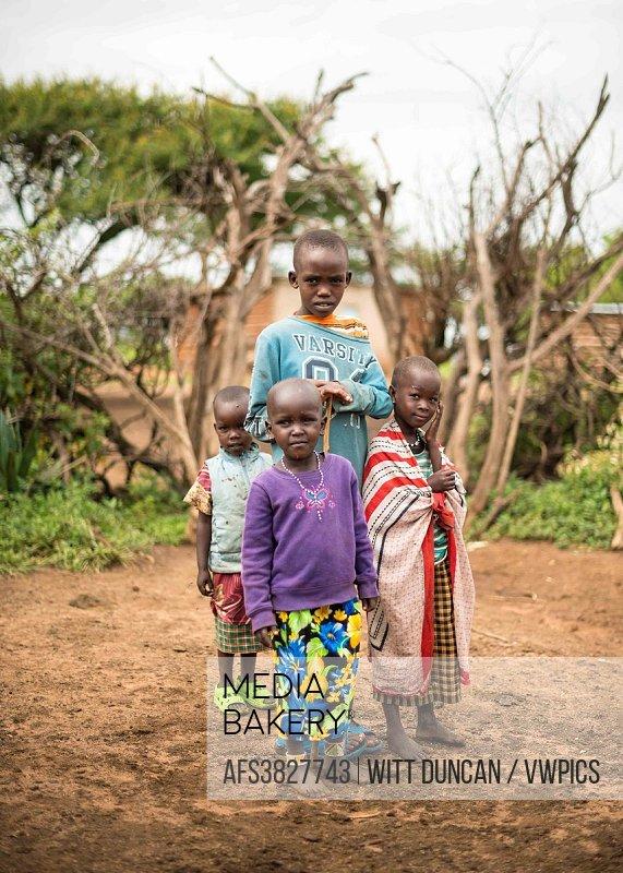 Four maasai children in their village.