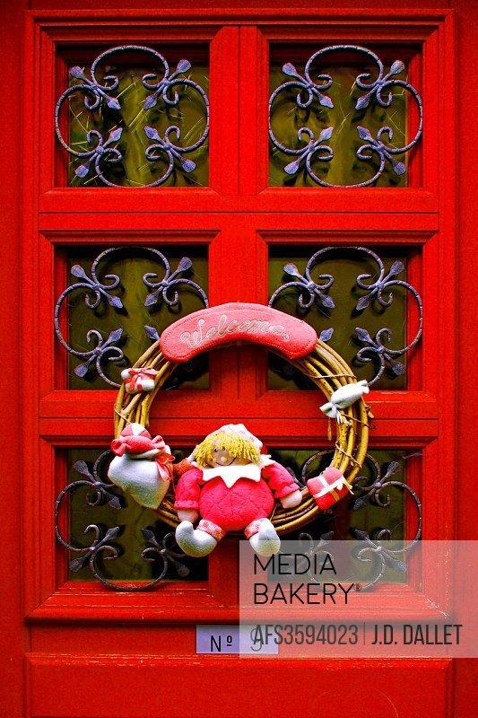 Welcome sign on red door
