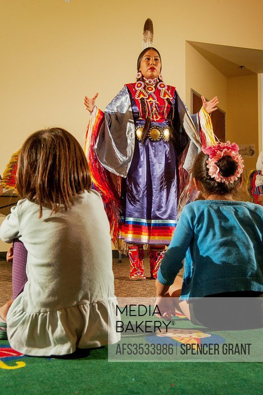 Before a youthful audience, a Navajo Indian explains the female-only Fancy Shawl Dance wearing tribal costume during a performance of Native American ...