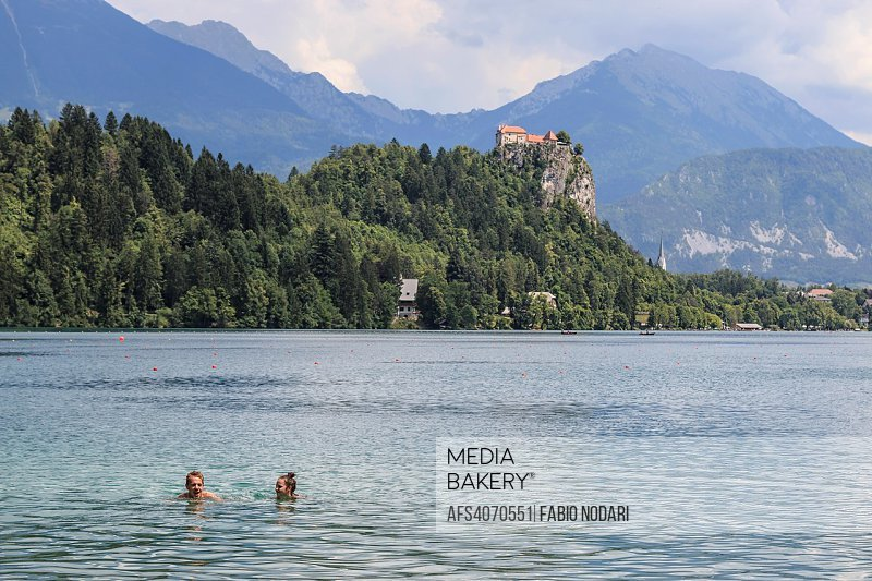 People swimming in Lake Bled with Bled Castle on background.