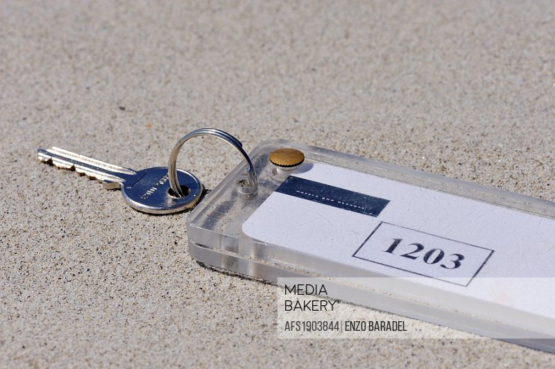 Hotel room keys abandoned on the beach