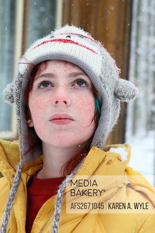 freckled girl in sock-monkey hat and yellow parka looking up with somewhat stern expression at snowflakes