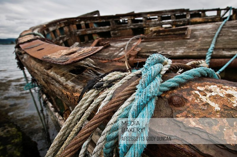 Ropes and cables hang from edge of abandoned fishing boat, near Salen, Isle of Mull, Scotland