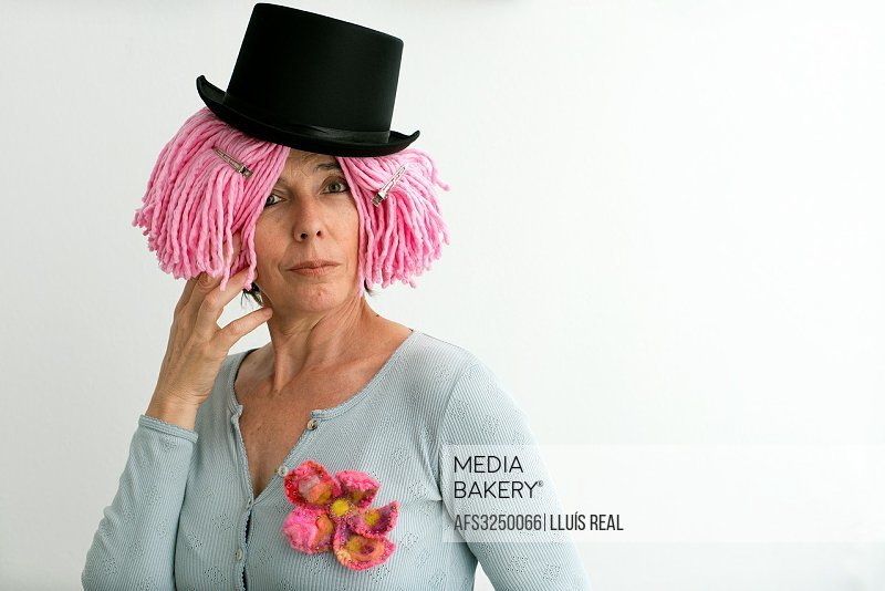 Portrait of Caucasian woman, fifties, pink wig and black hat.
