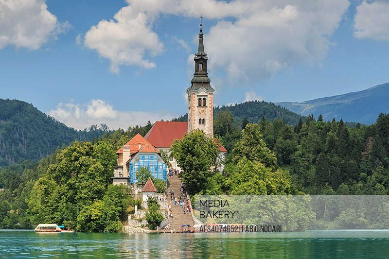Close up of the church in the center of Bled Lake with several tourists walking by.