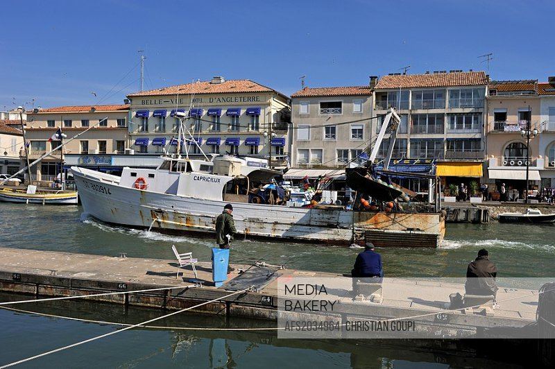 fishermen in the port of Grau du Roi, with background the Bellevue hotel where Ernest Hemingway stay in 1949, Gard department, Languedoc-Roussillon re...