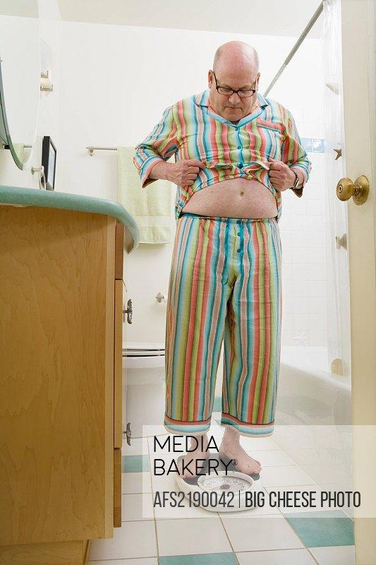 Man weighing himself in bathroom