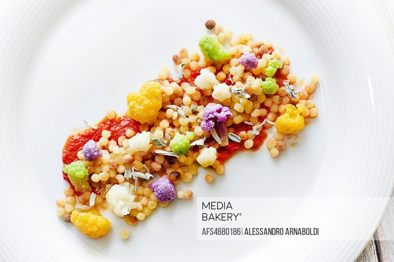 Fregula traditional kind of pasta from Sardinia with multicolor cauliflower and tomato sauce