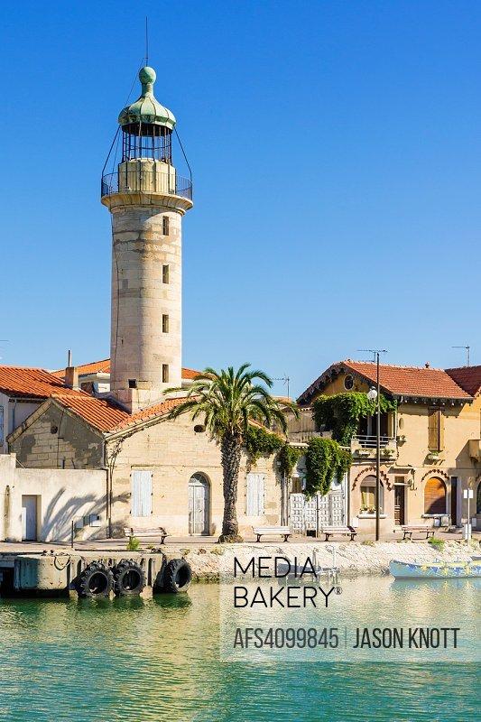 The landmark stone lighthouse along the Chenal Maritime, Le Grau-du-Roi, Gard, Occitanie, France.
