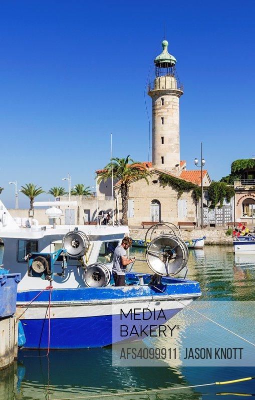 Moored fishing boats and the landmark stone lighthouse along the Chenal Maritime, Le Grau-du-Roi, Gard, Occitanie, France.