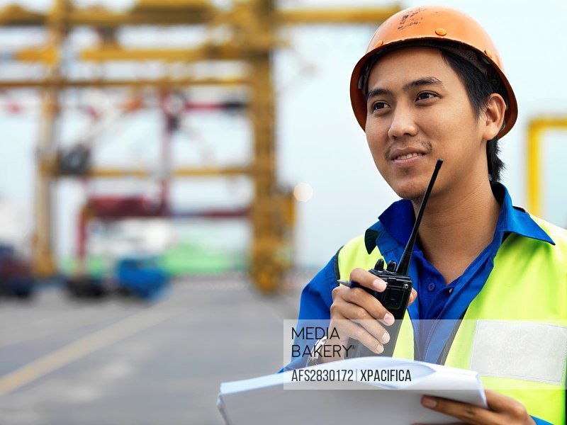A port worker talking over and radio overseeing work at a commerical container and Palm Oil port in Johor, Malaysia
