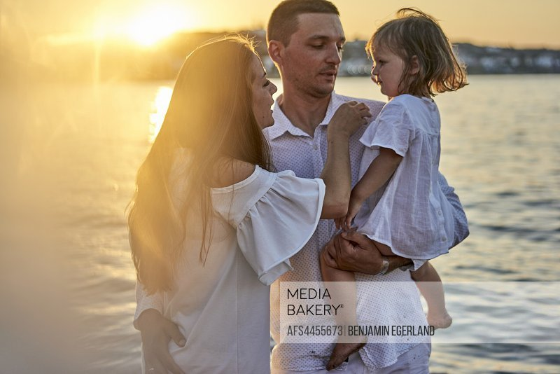 family, parenthood, sunset, candid, unposed, real people. In Chersonissos, Crete, Greece