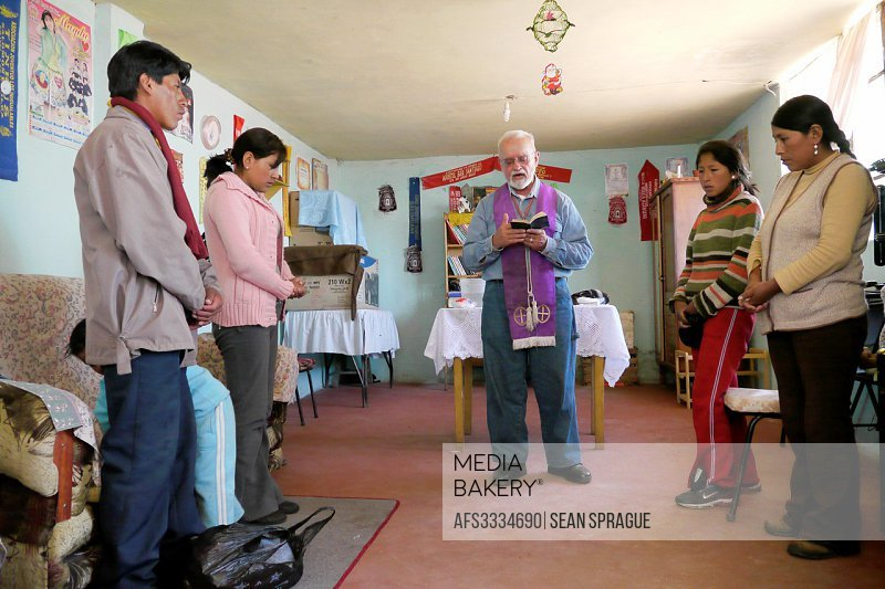 PERU. Americam missionary priest giving sacrament of the sick and house blessing for the Yucra Machacha family, Jayllihuaya, Puno.