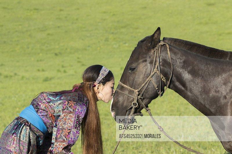 China, Inner Mongolia, Hebei Province, Zhangjiakou, Bashang Grassland, Mongolian woman with her horse.