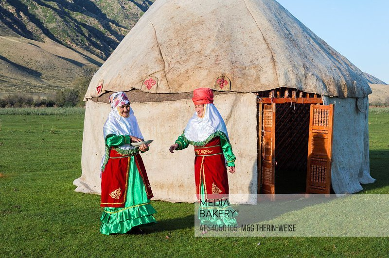 Two Kazakh women in traditional clothes in front of a yurt welcoming guests with candies, For editorial Use only, Sati village, Tien Shan Mountains, K...