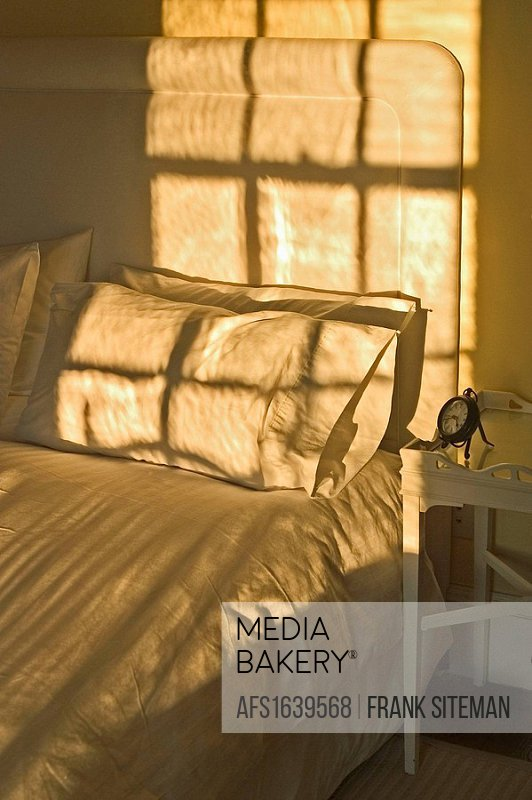 Late afternoon sunlight raking over bed and pillows with shadows of the window, next to a nightstand with a silhouetted alarm clock