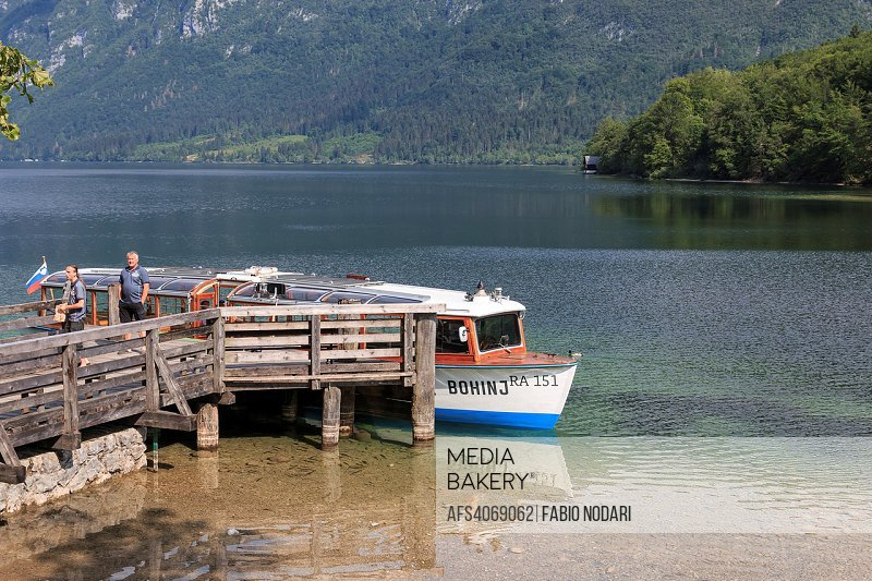 Tourists on a small boat in lake Bohinj, a famous destination not far from lake Bled.