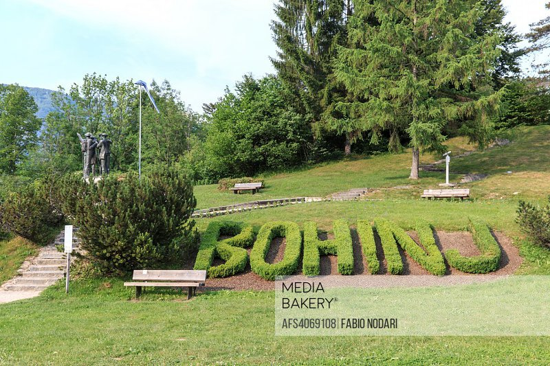 Statue of the four men in the center of Bohinj, with Bohinj text on foreground Slovenia.
