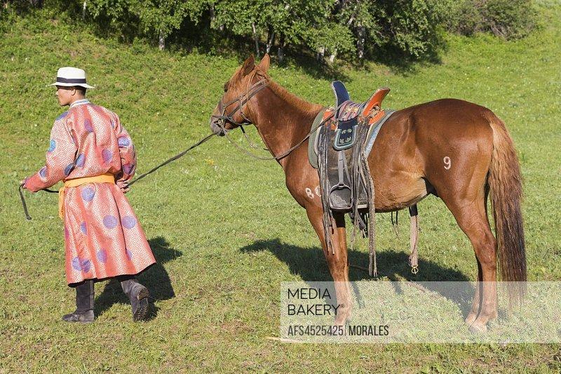 China, Inner Mongolia, Hebei Province, Zhangjiakou, Bashang Grassland, Mongol with his horse.