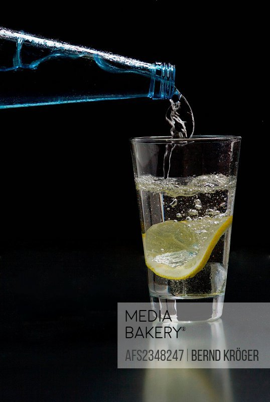 Mineral water is poured into a glass with ice and lemon