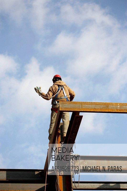 Construction steel worker walking on steel beam
